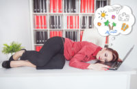 Tired businesswoman sleeping on the table and dreaming about vacation in office